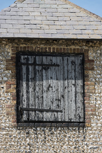 Old Barn Door: A loft door on an old cobblestone barn on a farm in Sussex, England.