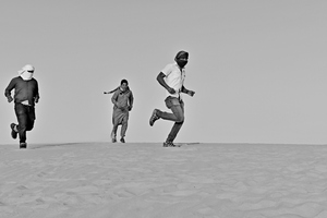 Men running in the desert sand: Men from India are running and playing in the desert sand in Saudi Arabia. Sunlight is strong and sky is blue and the desert men are having fun like desert people in the hot desert. The run and have a good time on the sand.