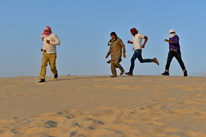 Men running in the desert sand