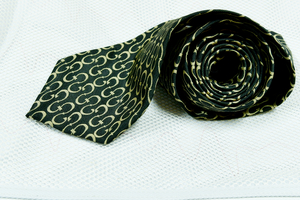 close up of a men's luxury tie: Luxury Tie for men. in Black colour, by a famous fashion company. Men's fashion, and dressing accessories. Display of necktie on close up photo