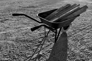 Wheel Barrow in B&W: Black and white photo of a wheel barrow loaded with soft wood and ready for transport !. Art and artwork image or wall art and printed art, or websites background for web designers