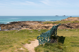 Sea view seat: An old ornamental bench on the coast of Cornwall, England.
