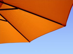 Sunny umbrella: orange beach umbrella in blue sky