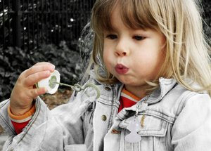 Blowing bubbles: Small girl blowing bubbles.