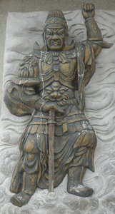 Stone Warrior: stone carving on foot of a Buddha statue.