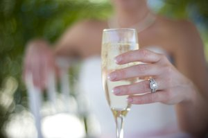 Champagne: Holding a glass of champagne.