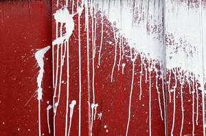 Splatter: White paint splattered on a red warehouse door.