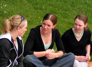 Teen talk: 3 teenage girls.  Must be a fascinating conversation judging by their expressions.  Summer picnic on the grass.  Isn't it funny to see that even when allowed to wear what they want, teens still seem to wear