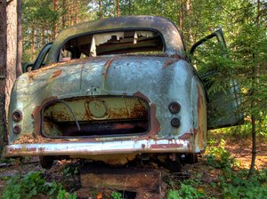 Disintegration - HDR: Old car lying in a forest. The picture is HDR using 5 images.