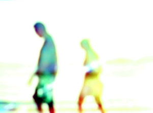 Couple Walking on the Beach- A: Hazy figures on a hot, sunny day at the beach.
