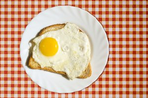 Fried egg: Fried egg with bread on checkered tablecloth