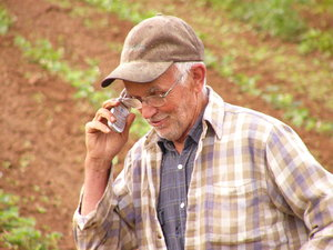 Farmer Clem meets the 21st C: Farmer cultivating crops by hand because his horse died ... as his wife calls him on his cell phone