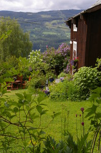 Old farmhouse: An old faarmhouse with the front garden and the valley of Valdres, No, in the background