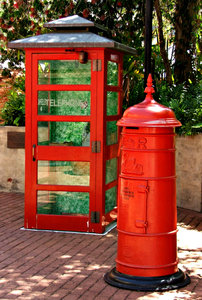 communicate in red: historic and traditional red telephone booth and postal letter collection box