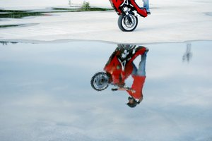 Biker stunt: Biker stunter reflection in water