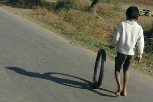 Boy pushing wheel: A boy in rural India on an imaginary car-drive on a road with little traffic.