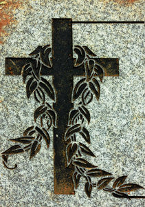 Etched cross on headstone: Graveside headstone with a cross etched in the stone