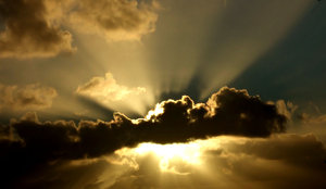 sun rays & storm clouds: golden sun rays spreading from behind dark storm clouds