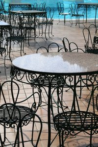 Cafe terrace: Cafe tables and chairs on a terrace beside a swimming pool in Madeira.