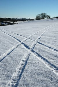 Crossing tracks: Tractor tracks in a snowy field in Devon, England.