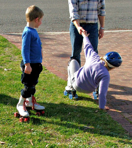 helping hand: fallen roller skater helped up by father