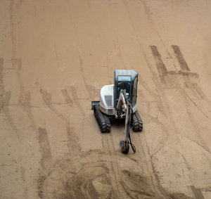 playing in the sand: a mini-excavator and sand.