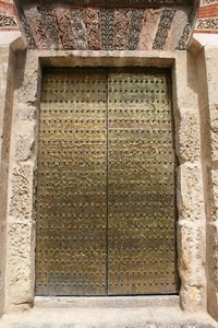Old brass door: An ancient wooden door, coated with brass, in the wall of a former mosque in Cordoba, Spain.