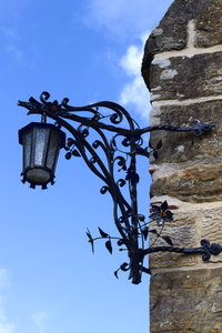 Ornate lamp: An ornate cast iron lamp on the wall of a church in Sussex, England.