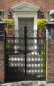 Wrought iron gate: An ornate wrought iron gate to a formal house in England.