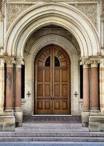 arched entrance: closed doors on historic building's stepped arched entrance