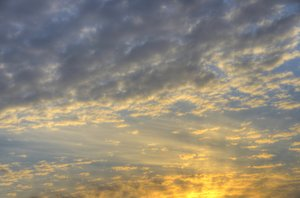 Morning sky scape: Early morning sky with sunbeams, clouds and burning yellow colors. The image is HDR.