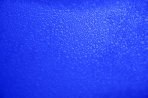 Bubble Texture: A dark blue closeup view of bath bubbles on water, suitable for a background.