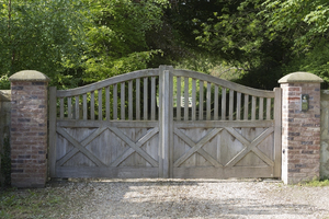 Driveway gates: Ornamental oak gates to the driveway of a rural estate in West Sussex, England.