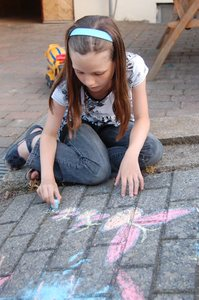Pavement artist 2: Young girl drawing on a pavement, with permission, with chalks.