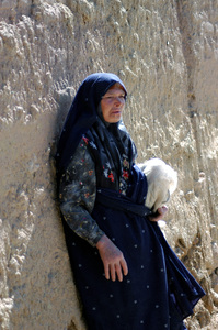 Old Woman: Old persian woman leaning  the wall.