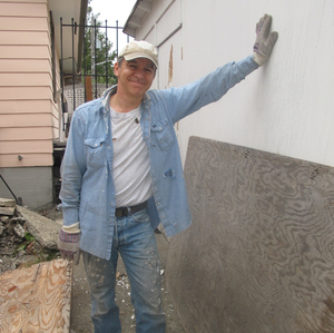 Happy handyman: A satisfied mature man in well-worn and messy work clothes stands amid debris of a construction project.