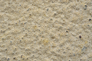 Texture - plaster: Outdoor wall with yellow plaster, sand and small stones.