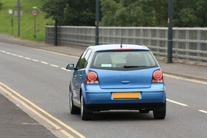Blue car: Rear view of a blue car (VW Polo) driving on a British road