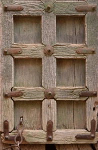 Strong door 2: Detail of an old wooden door strengthened with metal rivets and plates. From a fort in Rajasthan, India.