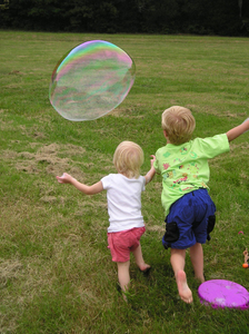 Kids chase a bubble at a famil