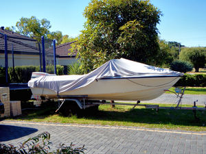 undercover boat1: a sign of status/prestige a motor boat parked in front yard
