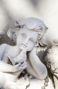 Angel with little bird: Cemetry ornament of a little angel