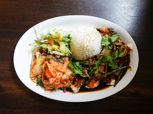 vietnamese fillet of salmon: vietnamese fillet of salmon served with rice, vegetables, salad, kimchi and a tasty sauce
