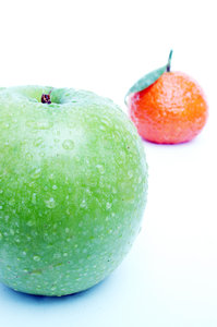 Apple and mandarin.: A fresh green apple with a mandarin on the background.