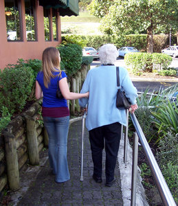 Helping the elderly: young person giving elderly lady a hand. Submitting this because of community/generation application.