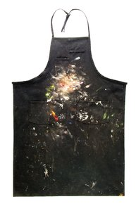 Artist Bib: I black bib used to protect an artist from the paint you see on it. Pinned flat to the wall, the bib has some interesting paint spatter and smudges.