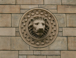 Lion head: An old Victorian ornamental terra cotta sculpture of a lion's head on a wall in London, UK.