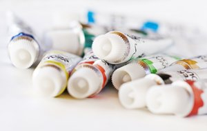 Paint tubes: small paint tubes on white background. Shallow DOF.