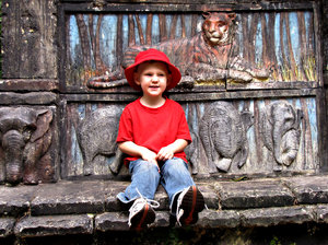 tiger watch: young boy in red and blue on steps of animal memorial with bas relief images of tiger and elephants