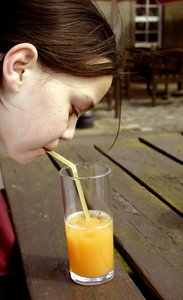 orange juice: Child drinking a glass of juice through a straw